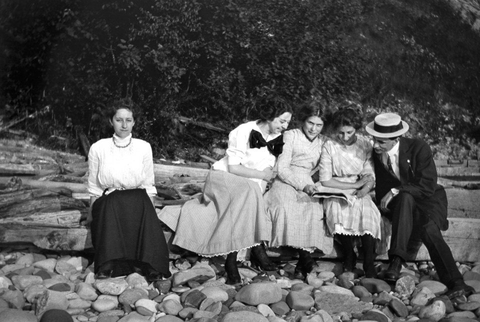 Social anxiety: it's not new!! ca. 1905 --- One women seems left out of the crowd while sitting on a log, ca. 1905 --- Image by © Kirn Vintage Stock/Corbis